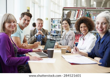 Group Of Mature Students Collaborating On Project In Library #284521601