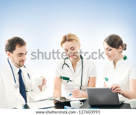 Group of medical workers discussing in office over the blue background