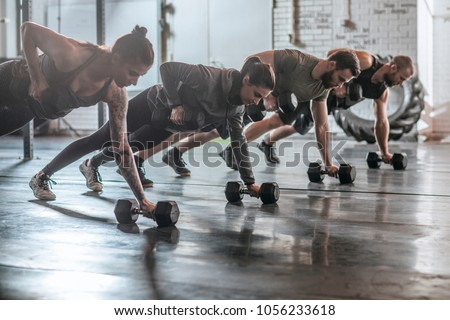 Group of men and women doing workouts together at gym.