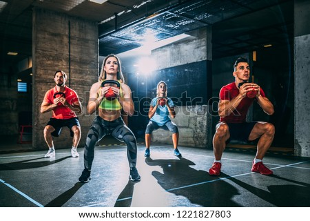 Group of men and women exercising with kettlebell.