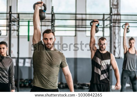 Group of men and women lifting weights at crossfit training at gym. Photo stock ©