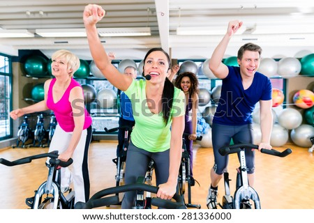 Group of men and women on fitness bikes in gym, diversity people, old, young, black and white