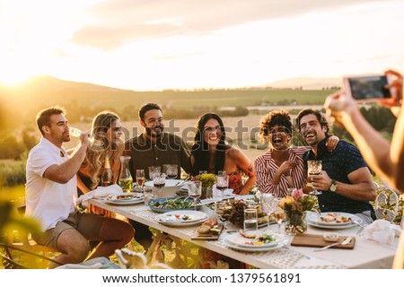 Group of men and women posing for a photograph during an outdoor dinner party. Woman hands taking picture of her friends at dinner party.
