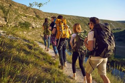 Group of men and women walk in a row along the trail during a walking tour of the mountains. Adventure, travel, tourism, hike and people concept. Camping season.