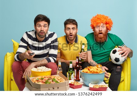 Group of men football fans watch with great surprise final match, shocked by favourite team loose, hold remote control and ball, stare at TV, drink cold beer, eat pizza, pose on yellow sofa.