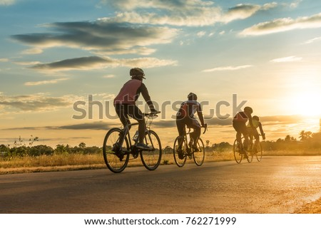 Group of  men ride  bicycles at sunset with sunbeam over silhouette trees background.