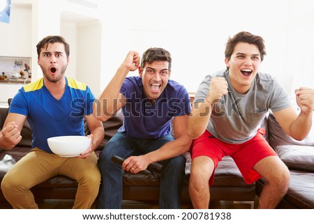 Group Of Men Sitting On Sofa Watching Sport Together