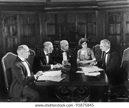 Group of men sitting with a young woman in a boardroom