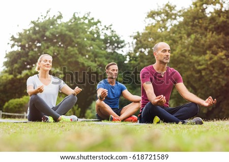 Group of middle aged people doing yoga sitting on grass. Three people practicing meditation and yoga at park on a bright morning. Mature woman and two mid men meditating together in a lotus position. Stock photo ©