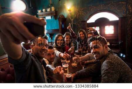 group of millennial people takes a selfie in a pub drinking beer and eating snacks