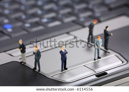 Group of miniature businessmen standing on a laptop. Modern business concept.