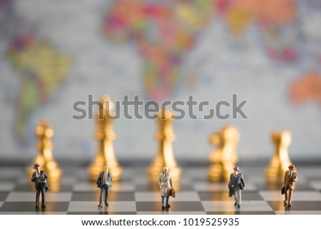 group of miniature businessmen walking in the chess board with the background is world map illustrate  business and leadership concept #1019525935