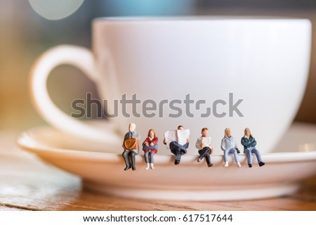 Group of miniature people figures sitting, waiting and reading newspaper and book on white plate of cup of hot coffee at coffee shop.