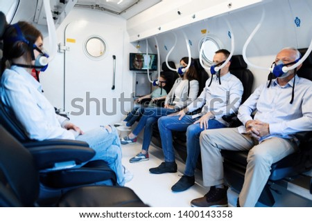 Group of mixed age people wearing masks while having oxygen therapy in hyperbaric chamber.  Stock photo ©