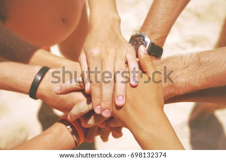 Group of Mixed Race Hipster Friends on the Beach with their Hands Stacked. Arms of Young People with on Stack. Lifestyle Team Building Concept. Thailand.