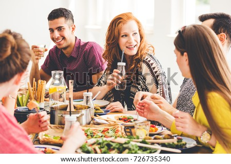 Group of mixed-race people celebrating vegan party at home, sitting at colorful table full of healthy snacks, salads and organic dishes