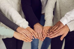 Group of mixed race people joining hands as symbol of team spirit. Concept of power, unity, corporate social responsibility, mutual support and reaching goals together. Human hands in close-up