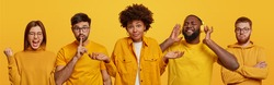 Group of mixed race people wear yellow clothes, make different gestures and express various emotions. Hesitant Afro American woman, ethnic guy listens music, Caucasian bearded man makes hush sign