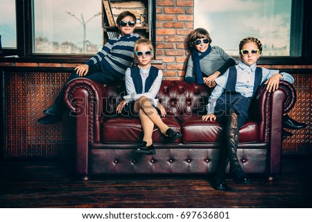 Group of modern children posing in school uniform and sunglasses in luxurious apartments. School fashion.