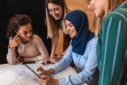 Group of modern multicultural young business women in casual wear discussing architectural designs in the creative office.