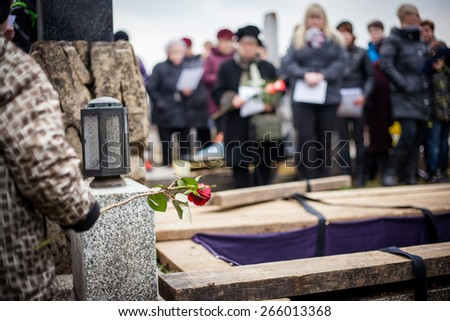 Group of mourners staying by the opened grave at a cemetery during a funeral ceremony