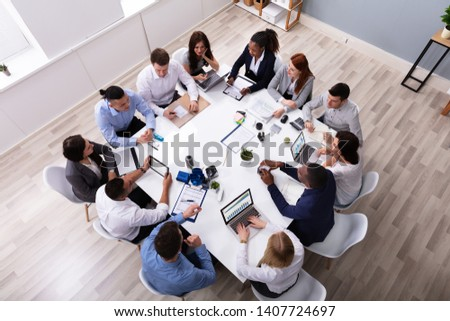 Group Of Multi Ethnic Business Team Sitting Together At Workplace In Modern Office stock photo