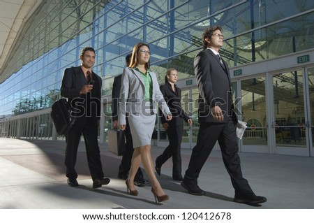 Group of multi ethnic businesspeople walking in front of office building
