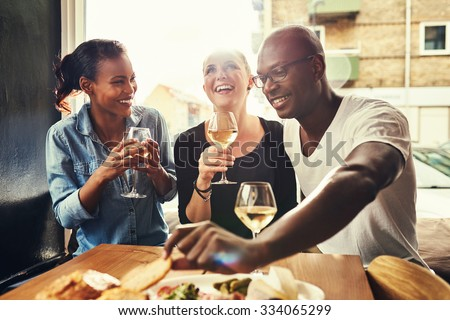 Group of multi ethnic friends drinking wine at a cafe outside Foto stock ©