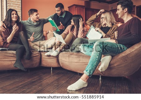 Group of multi ethnic young students preparing for exams in home interior.