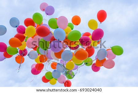 Group of multicolored helium filled balloons in the sky #693024040