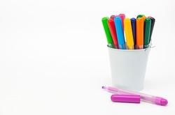 Group of multicolored markers in a white metal bucket on light background, one pen open cup, copy space. Drawing felt-tip pens, pencils, artists tools, creativity, hobby. Colorful school supplies.