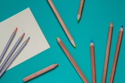 Group of multicolored pencils randomly on a turquoise background. Ten different used wooden colored pencils. View from above. Selective focus. Close-up.
