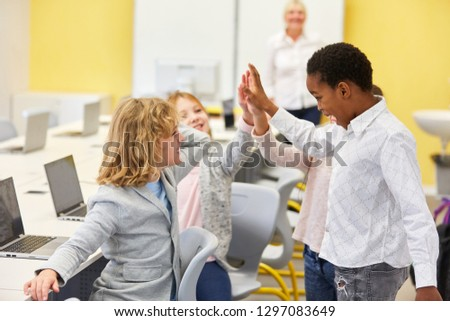 Group of Multicultural Kids Gives High Five in Computer Lessons