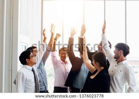 Group of multiethnic business men and woman raising hands up giving high five in sunny office - selective focus