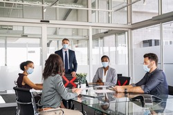 Group of multiethnic business people in meeting wearing face mask in conference room during covid19 pandemic. Business workers discussing strategy while wearing masks and keeping social distancing.