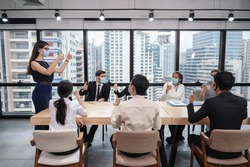 Group of multiethnic business people wearing face mask showing thumbs up and agree of business agreement during the meeting in new normal office while pandemic of Coronavirus, Covid 19