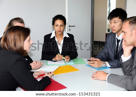 Group of multiethnic diverse young business people in a meeting sitting around a table with serious expressions discussing a new strategy or solution to a problem