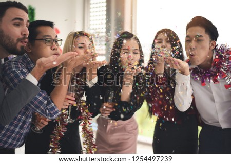 Group of Multiethnic Friends Celebrating Christmas New Year Party , Enjoy Throwing and Blowing Confetti in an Office After Work