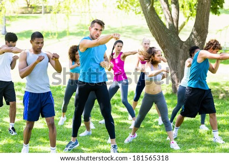 Group of multiethnic friends exercising in park - Shutterstock ID 181565318
