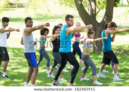 Group of multiethnic friends exercising in park - Shutterstock ID 182483915