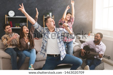 Group of multiethnic friends having cheerful party at home, playing the guitar, singing and dancing. Copy space