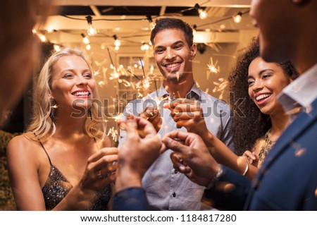 Group of multiethnic friends having fun with sparkling sticks during night party. Group of elegant women and men holding sparklers and celebrating the new year's eve. #1184817280
