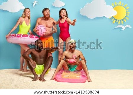 Group of multiethnic friends hve excited gaze, point and stare into distance, see something incredible, holds beach ball, inflated swim rings, have party at coast blue sea background with sun seagulls