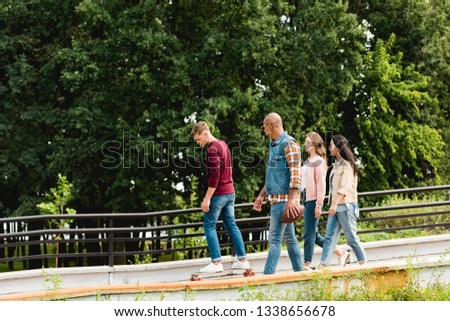 group of multiethnic friends looking at man riding skateboard in park