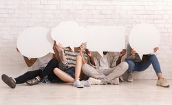 Group of multiethnic friends sitting on floor, hiding behind communication bubbles, panorama