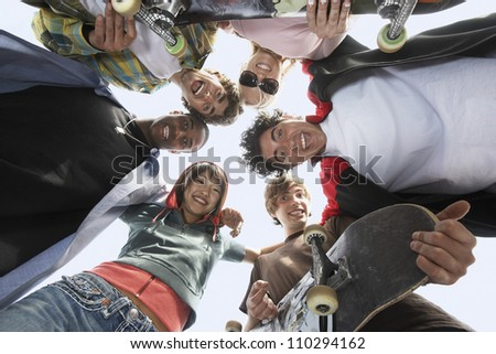 Group of multiethnic friends with skateboards forming circle from below