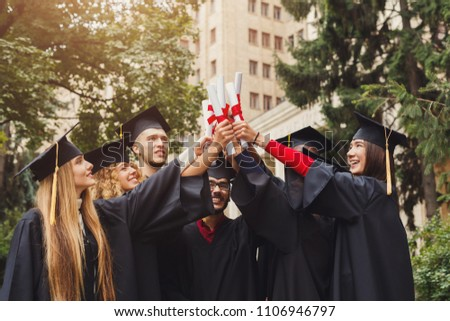 Group of multiethnic graduate students celebrating by cheering with their diplomas. Education, qualification and graduation concept.