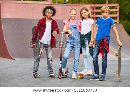 Group of multiethnic group of children standing with skateboards and looking at camera at skateboard park