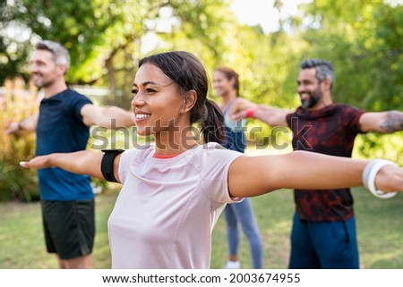 Group of multiethnic mature people stretching arms outdoor. Middle aged yoga class doing breathing exercise at park. Beautifil women and fit men doing breath exercise together with outstretched arms.
