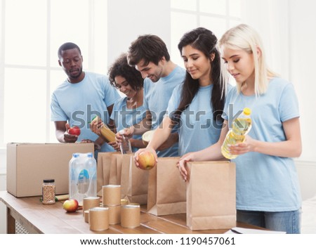 Group of multiethnic people packing goods for homeless in volunteer office, copy space